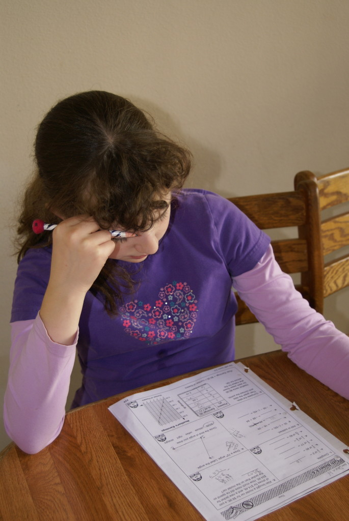A young girl reading a math assignment in her homeschool class